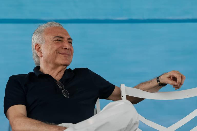 Presidente Michel Temer, de camisa polo preta e calça branca, sentado de pernas cruzadas e braço esquerdo apoiado numa cadeira branca